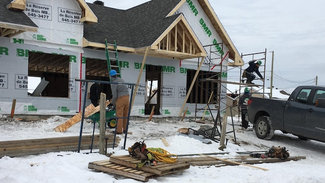 Des travailleurs construisent une maison à Saguenay.
