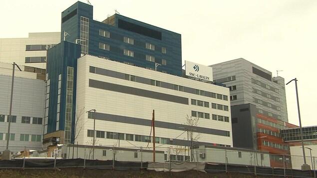 L'édifice du CUSM à l'époque de sa construction, avec des roulottes de chantier devant et une affiche de SNC-Lavalin sur un des bâtiments.