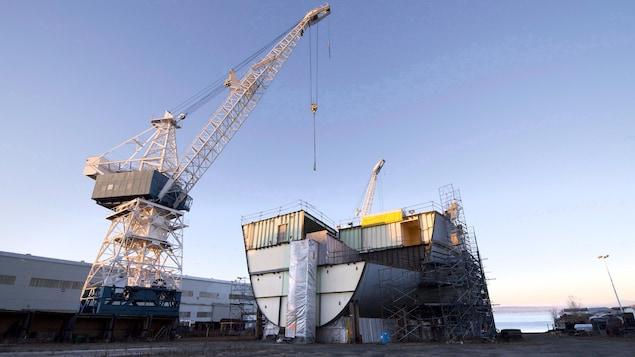 Une grue surplombe un bateau en construction.
