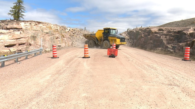 Un camion jaune sur une route en construction.
