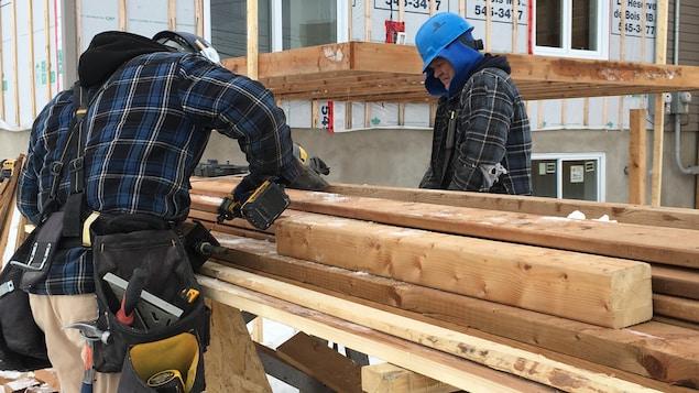 Des travailleurs de la construction dehors, en hiver.