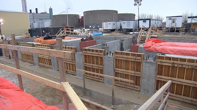 Un chantier de construction, où l'on voit des roulottes, de grosses structures et des panneaux de bois.