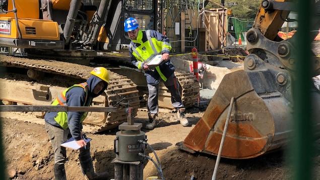 Deux ouvriers se tiennent à une certaine distance l'un de l'autre, aux côtés d'un bulldozer.