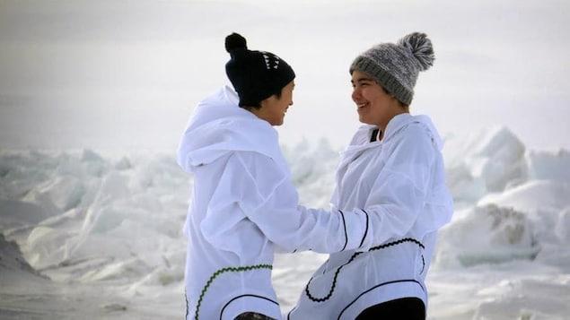 Les deux jeunes femmes sont face à face et se tiennent par les avant-bras, souriantes. Derrière elle, on voit un paysage enneigé et glacé.