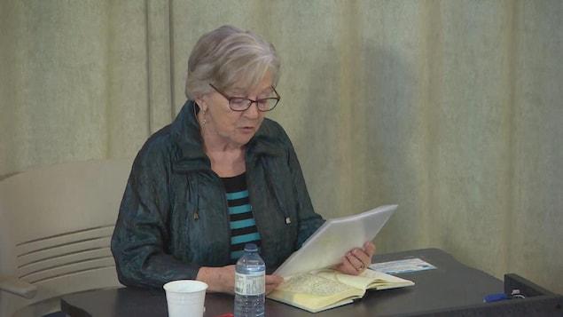 Une femme lit un livre assise à un bureau.