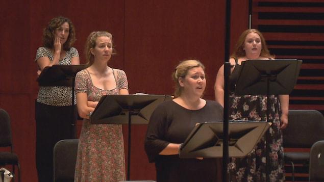 Des femmes chantent. Un pupitre est installé devant chacune d'elles.