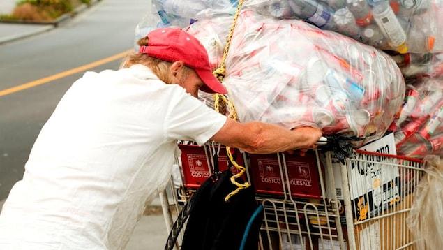 Un homme portant une casquette rouge pousse dans la rue un chariot rempli de gros sacs de bouteilles et de cannettes qui sont destinés à être recyclés.