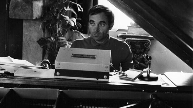 L'auteur-compositeur-interprète Charles Aznavour écrit ses chansons au piano.