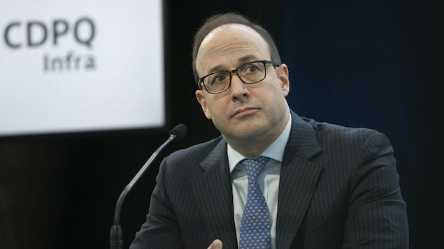 Charles Émond, assis derrière un micro durant une conférence de presse.