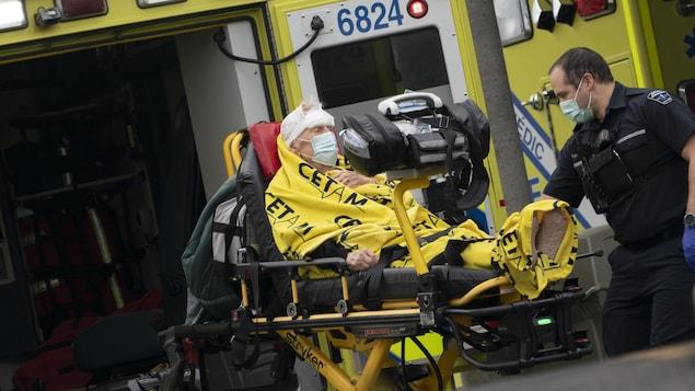 Un ambulancier s'occupe d'un patient allongé sur une civière près d'une ambulance dont la porte arrière est ouverte.