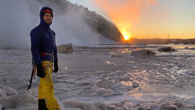 Charles Roberge en équipement d'escalade sur la glace, en bordure des chutes Montmorency et du fleuve, au lever de soleil