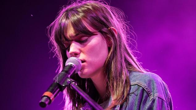 La jeune femme chante les yeux fermés avec un micro très près de sa bouche.