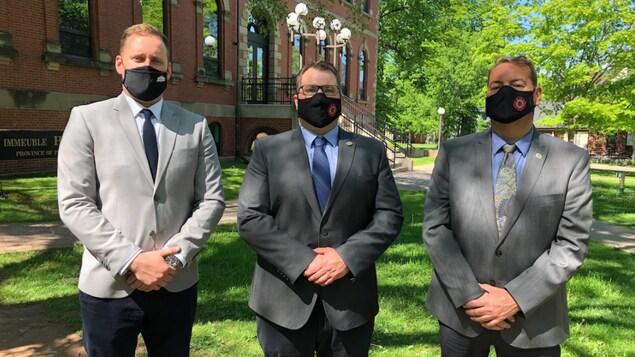 Les trois hommes devant l'édifice de l'Assemblée législative.