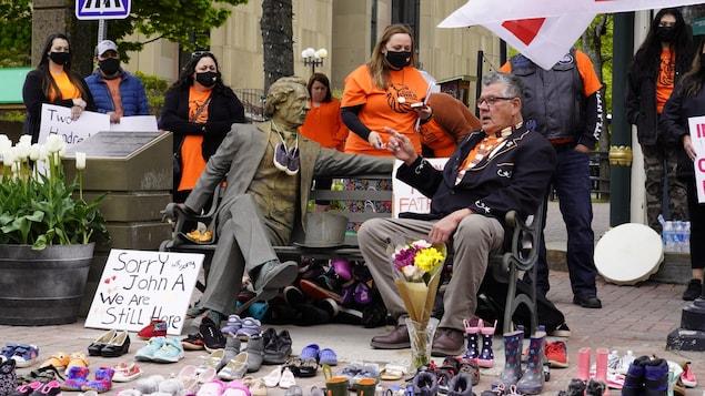 Des femmes et des hommes entourent une statue avec des paires de chaussures d'enfants.