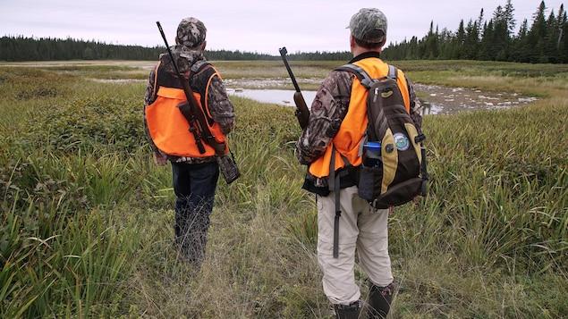 Deux chasseurs guettent l'horizon dans une clairière.