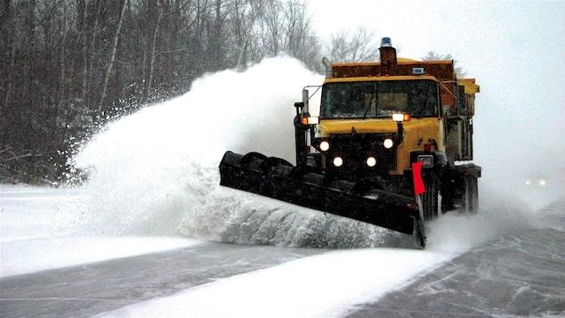 Un chasse-neige sur une autoroute projette une gerbe de neige dans le fossé.