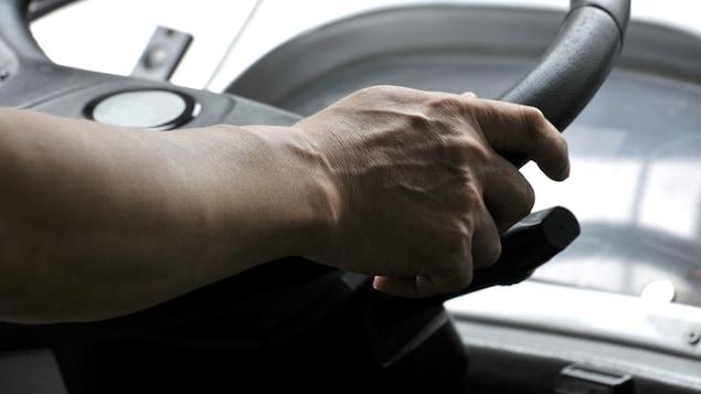 Un conducteur d'autobus, les mains sur le volant.