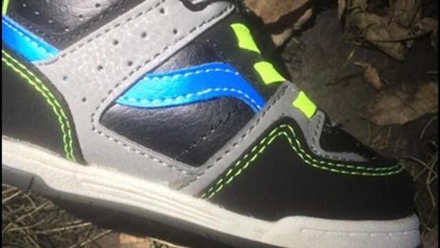 Une chaussure noire, grise et bleue avec des lacets jaunes