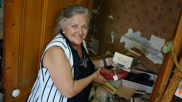 Une femme pose devant la porte ouverte d'un placard mural à moitié rempli de boîtes et de chaussures. La femme tient une boîte et une paire dans ses mains.