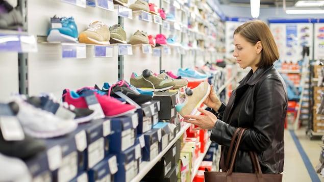 Une consommatrice examine une paire de chaussures sports