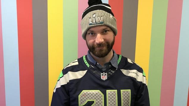 Un homme blanc avec la barbe et un bonnet et un maillot de football.