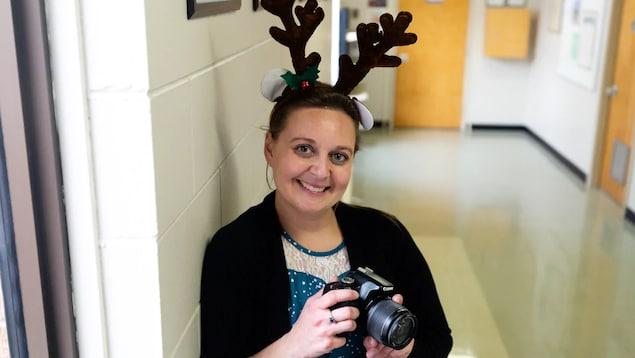 Chelsey Hicks pose souriante avec une caméra dans les mains et des bois des rennes sur la tête. Elle est dans le corridor d'une école.