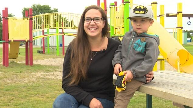 Une mère sourit à la caméra en enlaçant son fils, tous deux assis sur une table de pique-nique dans un parc.