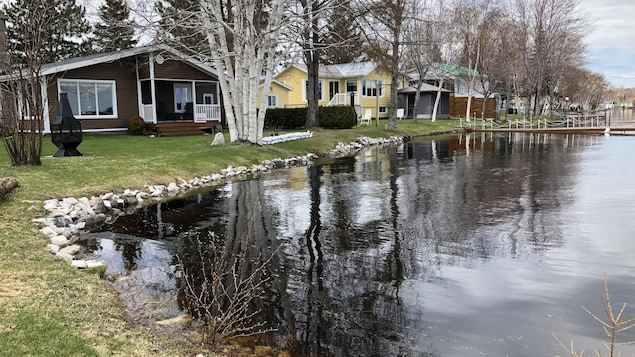 On voit plusieurs maisons situées tout près de l'eau.