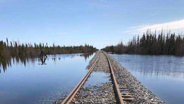 Un chemin de fer est à demi immergé dans l'eau, qui entoure la voie.