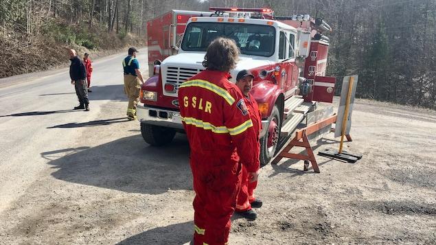 Des pompiers sont déployés le long du chemin pour assurer la sécurité dans le secteur.