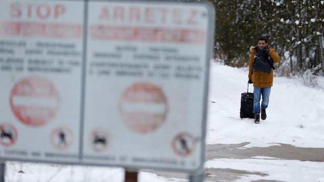 Un homme descend le chemin Roxham en direction de la frontière canado-américaine.