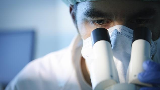 Un scientifique regarde dans un microscope.