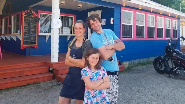 Les propriétaires du casse-croûte Chez Ginette et leur fille devant leur établissement fraîchement peint en bleu et rose.