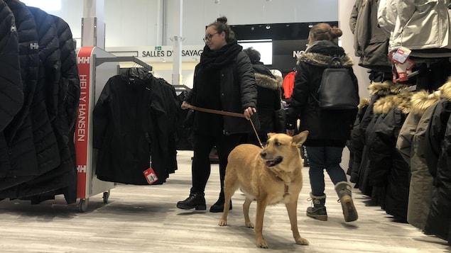 Une femme promène son chien dans un magasin du Quartier DIX30.