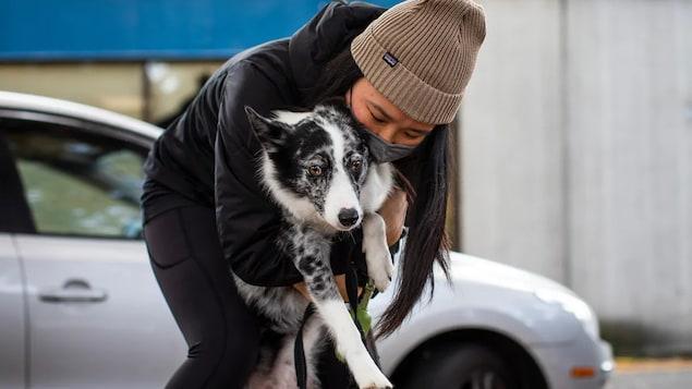 Une femme donne un câlin à son chien.