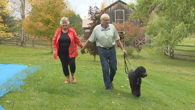 Photo d'un homme et d'une femme aînés qui font marcher un chien noir sur la pelouse à l'extérieur.