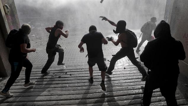 Des manifestants vus de dos lancent des projectiles.