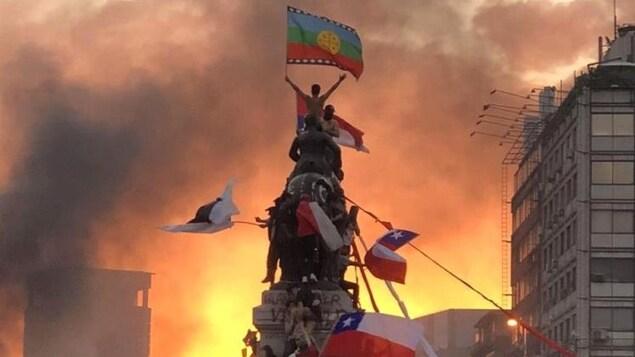 Une marre de manifestant grimpent à une statue à Santiago au Chili.