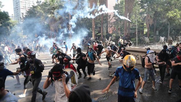 Des manifestants, portant des casques et des lunettes, poursuivis par des policiers.