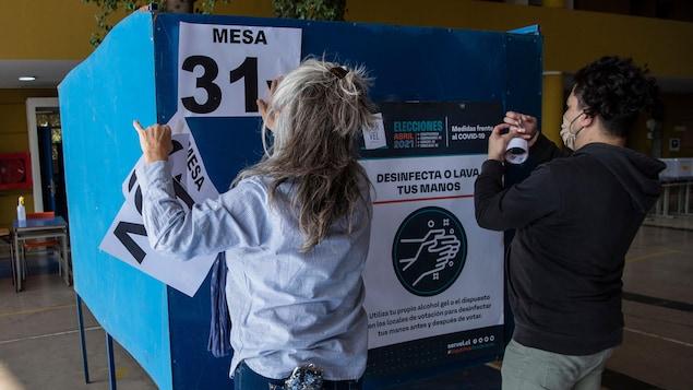 Des employés installent un bureau de vote à Santiago.