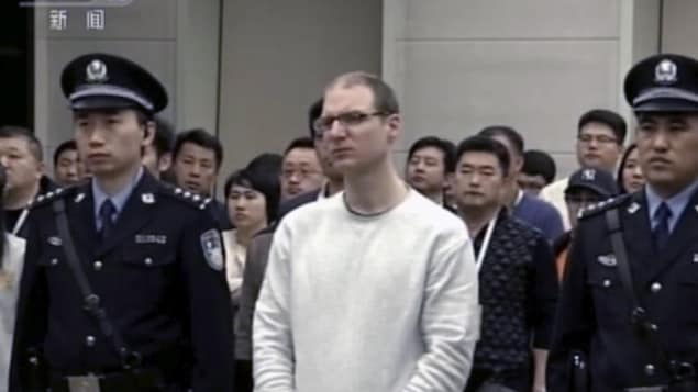 Flanqué de deux policiers chinois, un homme portant des lunettes et les cheveux très courts assiste à l'audition de son appel.