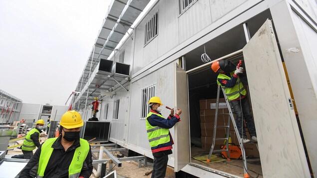 Des ouvriers portant des masques travaillent sur un immeuble.