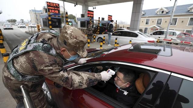 Le militaire pointe un thermomètre numérique sur le front d'un conducteur.