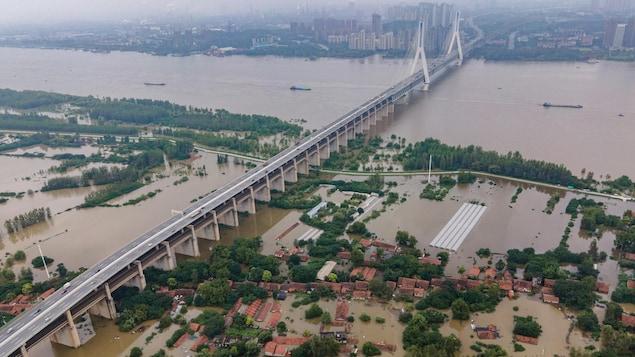 Vue aérienne du fleuve qui a débordé de son lit et qui est enjambé par un pont.