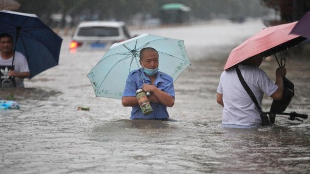 Des personnes portant des parapluies marchent dans l'eau jusqu'à la taille.