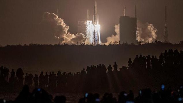 Une fusée s'élance dans le ciel, la nuit.