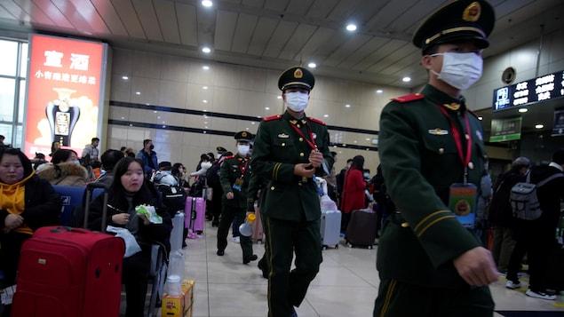 Des policiers portant des masques médicaux marchent dans une gare de Shangai.