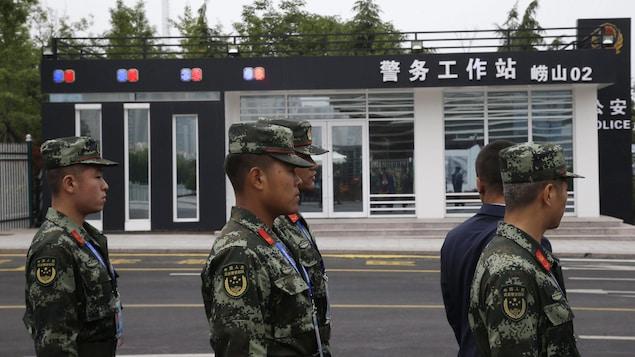 Des soldats chinois se tiennent près d'une station de police dans la province de Shandong.