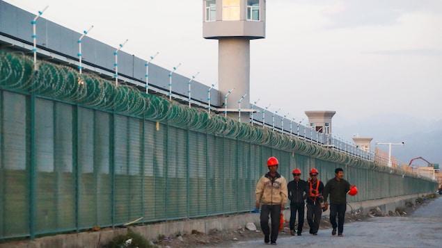 Des travailleurs chinois marchent le long d'une haute clôture ponctuée de mirador.