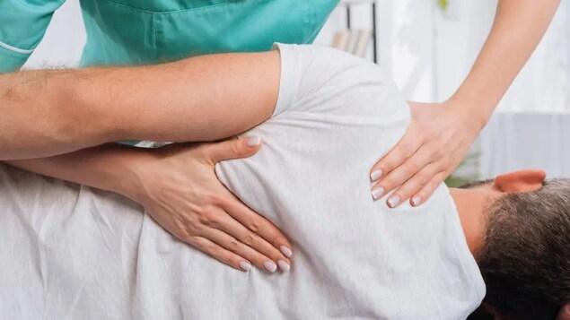 Une femme effectue un traitement de chiropratique sur un patient.